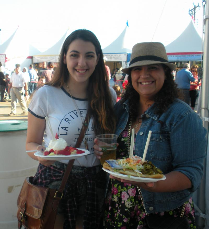 Chelsy and Jasmine Glenn are enjoying a family tradition they've kept since Chelsy was 4 years old- ordering their favorite dish from International Food Row on opening day at Festival of the Arts.