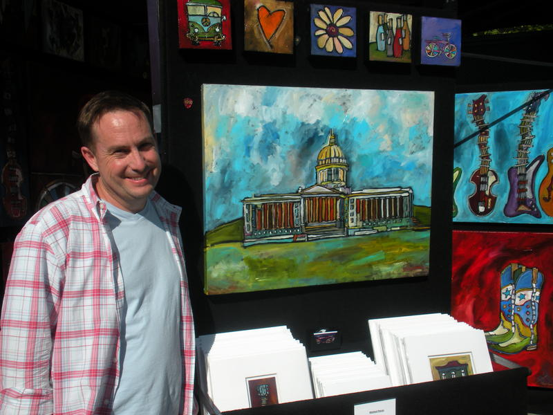 Michael Holmes stands beside his painting of the Oklahoma state capitol building. His is one of 141 artist booths at this year's Festival of the Arts.