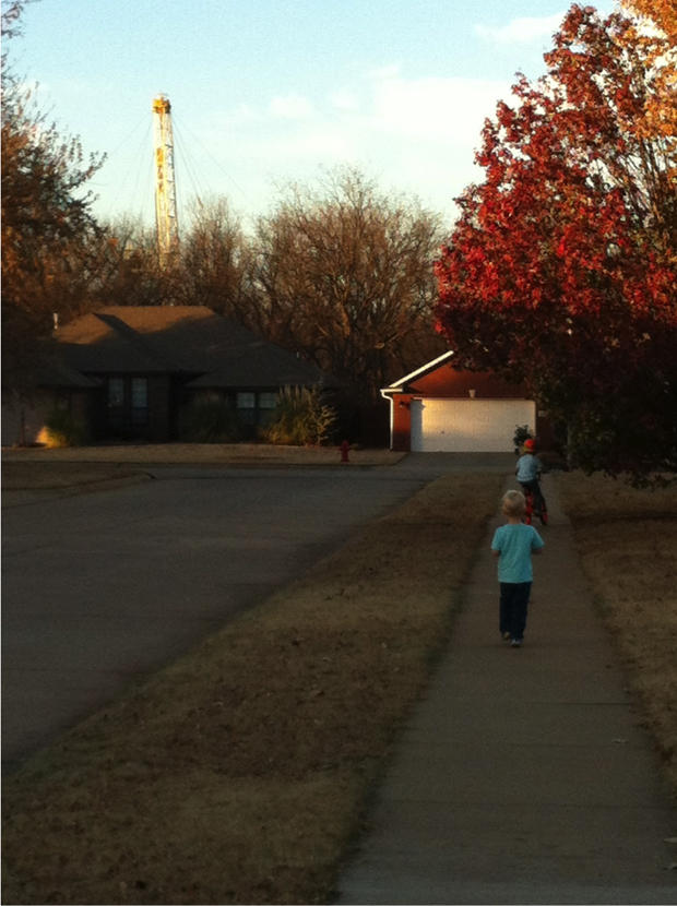 Tammy Mix's sons play on the sidewalk as a drilling rig peeks above the tree line behind her Stillwater home.
