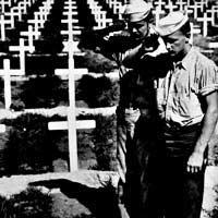 Troops salute a grave in a cemetery marked with crosses