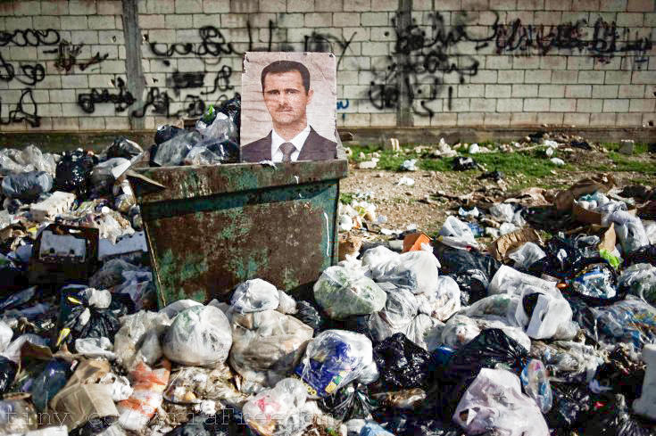 A portrait of President Bashar al-Assad among the trash in the Syrian city of al-Qsair in 2012.