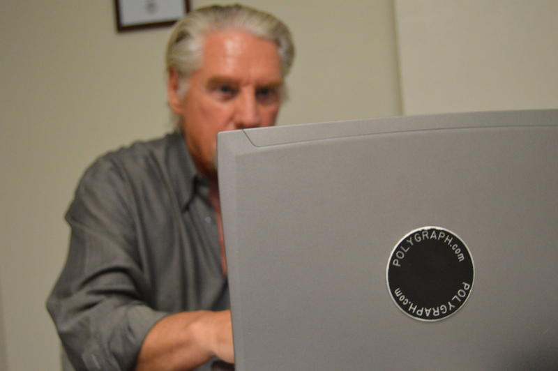 Doug Williams examines a polygraph test on his computer.