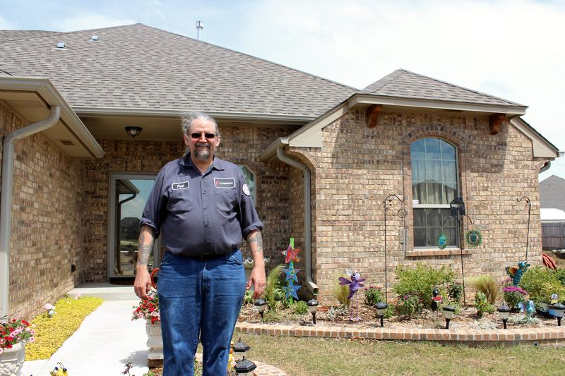 Paul Phillips stands in front of his home. He rebuilt on his lot after the 2013 tornado destroyed his house.