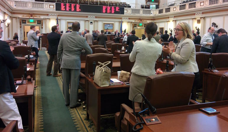 State Reps. Elise Hall (far right) and Katie Henke (center) applaud as the state House adjourns sine die Friday afternoon.