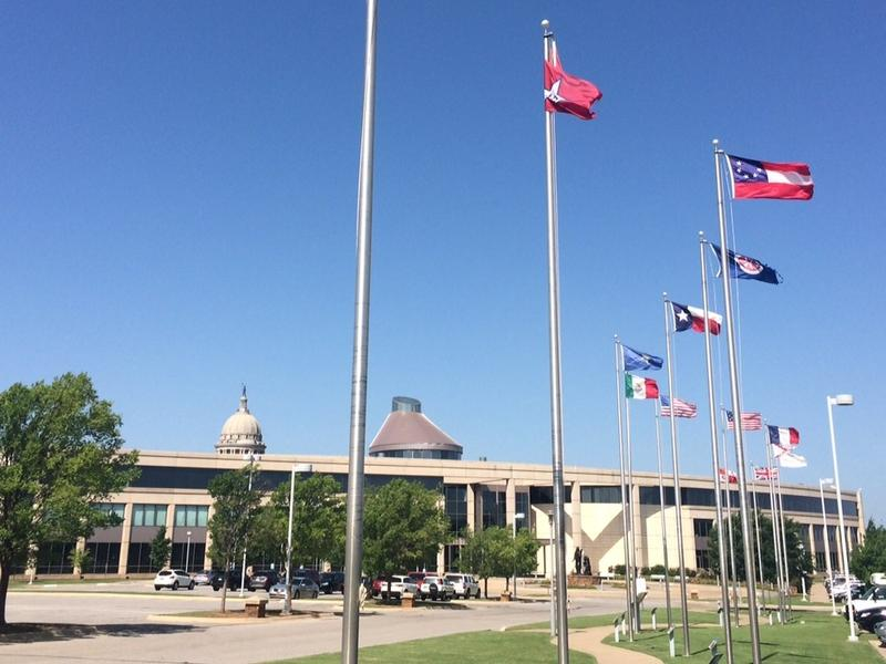"The 14 flags at the Oklahoma History Center in Oklahoma City. The Confederate ""Stars and Bars"" flag occupies the third pole from the front."