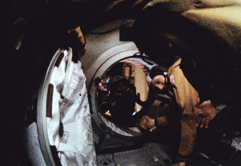 Oklahoma native Gen. Thomas Stafford (foreground) and Soviet cosmonaut Aleksei Leonov shake hands as they open the hatch between the Apollo command module and the Soyuz 19 spacecraft in July, 1975.