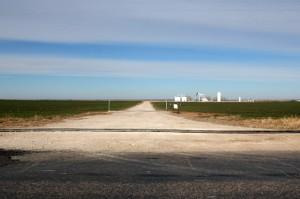 A water line for hydraulic fracturing crosses an oil-field access road in Woods County, Okla.