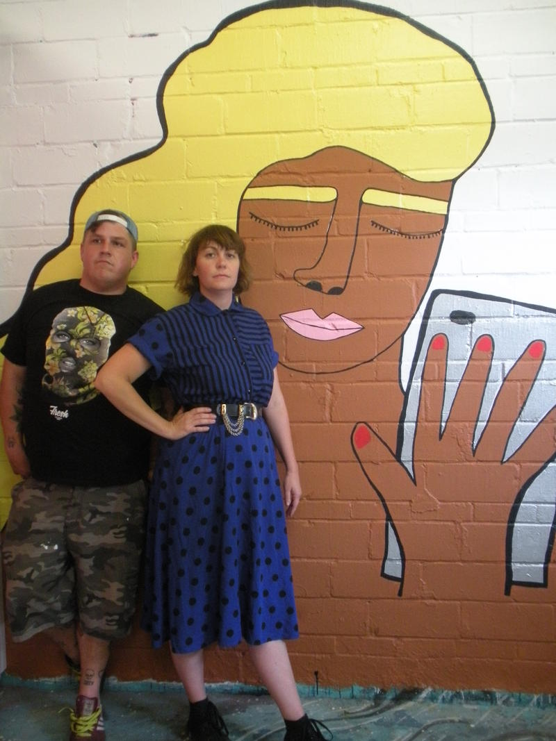 Ross Adams invites a fresh artist each month to cover the walls of Tall Hill Creative, the private studio he shares with Jason Pawley at 3421 N. Villa Ave. Here he poses with June artist Melissa Jacobs.