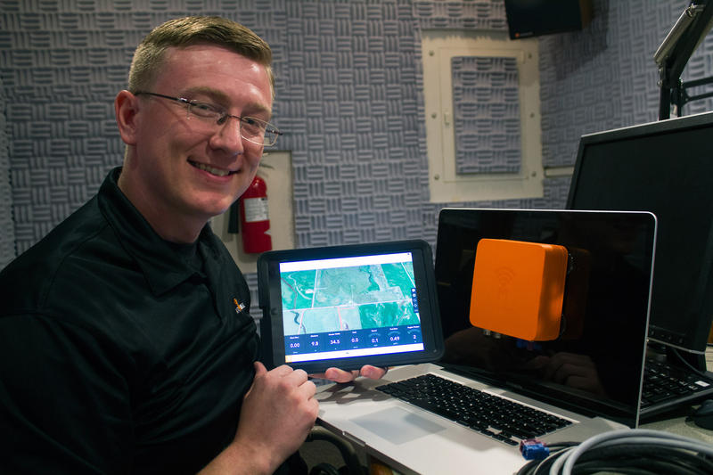 Heath Gerlock, a founder of Farmobile, shows the orange box device that can feed farm data directly to a tablet, smartphone or computer. Gerlock pictured in the Iowa Public Radio studio in Ames.