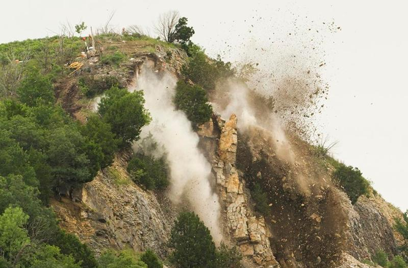 Engineers and demolition experts blast unstable rock from a formation in the Arbuckle Mountains after last month's rockslide along Interstate 35