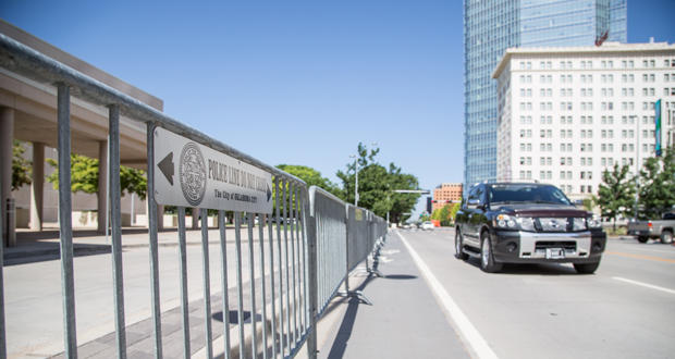 A motorist drives by a police barricade placed along Sheridan Avenue in downtown Oklahoma City in advance of a visit from President Barack Obama Wednesday.
