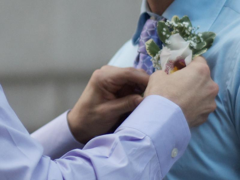 A man pinning a boutineer on his husband during a gay wedding in New York City.