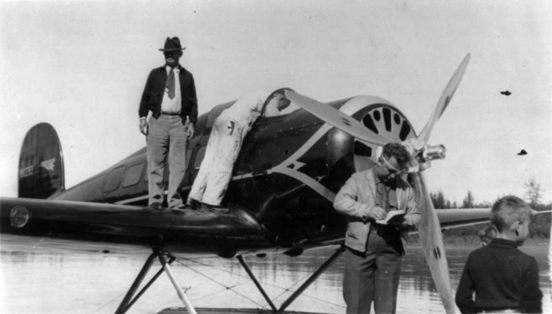 Will Rogers stands on the wing of a seaplane, with Wiley Post in front of the propeller, August 1935.