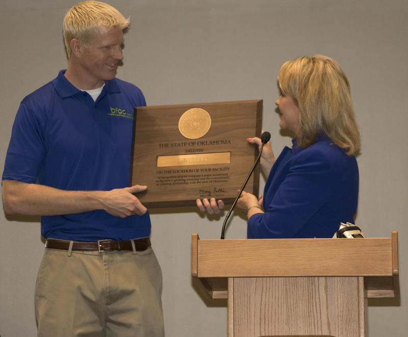 Gov. Mary Fallin presents BFAC.com President and CEO Brad McMullan a plaque from the Oklahoma Department of Commerce during Friday's announcement.