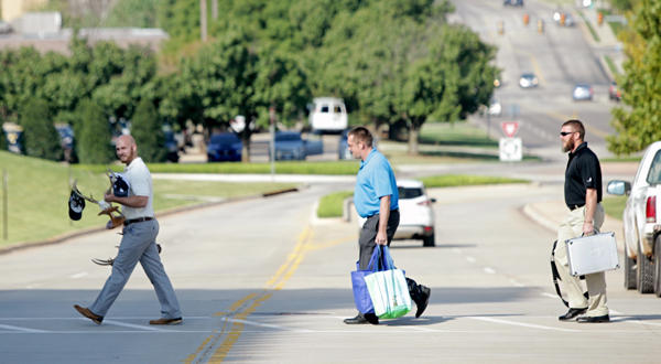 Chesapeake Energy employees leave buildings after layoffs were reported Sept. 29, 2015.