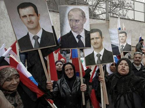 Syrian protesters hold signs with the faces of president Bashar al-Assad and Russian President Vladimir Putin in Damascus - March 4, 2012