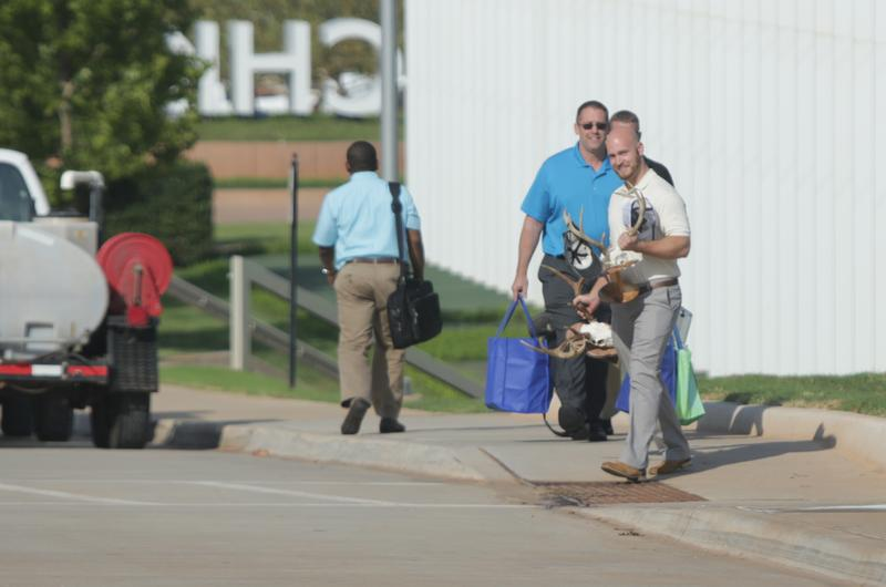 Former Chesapeake Energy employees leave the building with their belongings after the Sept. 29, 2015 buyouts.