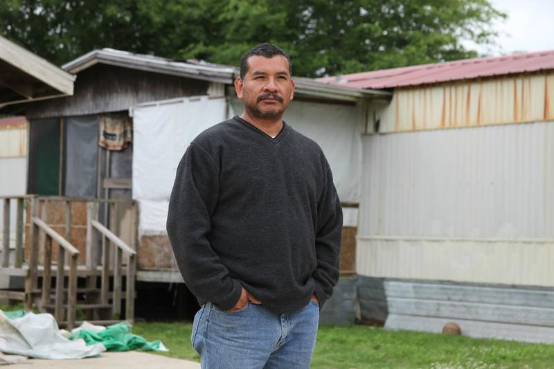 Former migrant farmworker Angel Castro stands in front of his old trailer in a neighborhood housing many immigrant farmworkers.