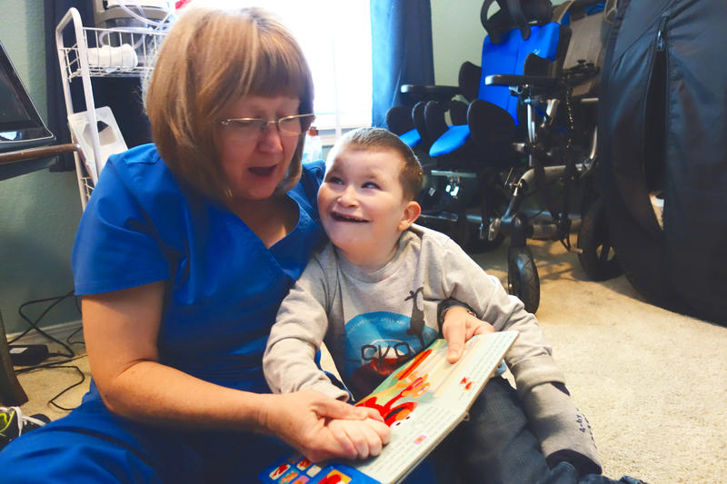 Home health nurse Rita Nuss reads a book to 9-year-old Josiah Melton, who has  chromosomal disorders and is on the developmental disabilities services waiting list.