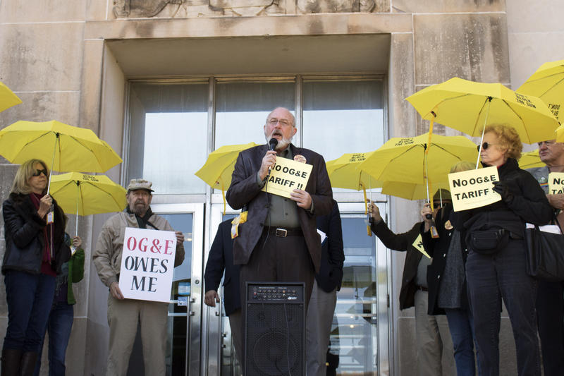 The Rev. Dr. Bruce Prescott speaks during Tuesday's protest on the steps of the Oklahoma Corporation Commission as other demonstrators hold signs voicing opposition to OG&E's demand charge proposal.