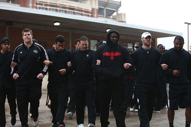 Sterling Shepard, Ty Darlington, Zach Sanchez, Bob Stoops, Charles Tapper, Trevor Knight, and Eric Striker walk arm-in-arm to protest campus racism in March 2015.