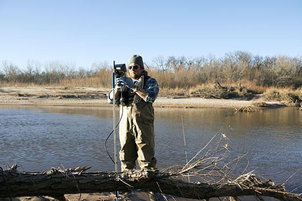Oklahoma Water Resources Board project coordinator Jason Murphy samples water in the frigid Canadian River east of Oklahoma City.