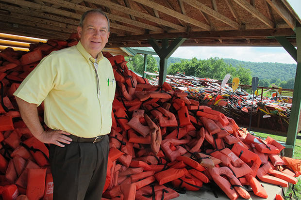 Ed Fite, executive director of the Oklahoma Scenic Rivers Commission, stands next to a mountain of life vests at one of the resorts on the Illinois River.