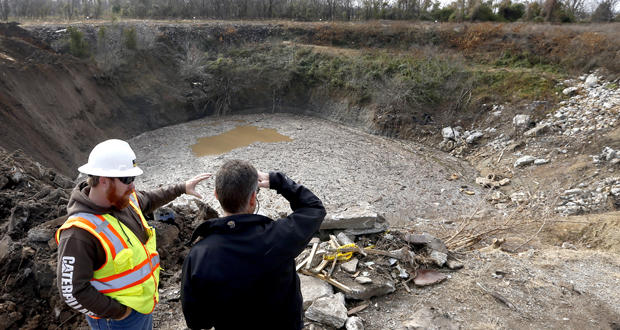 Cory Moates, owner of Moates Excavating, left, and Tim Kent, environmental director of The Quapaw Tribe of Oklahoma, inspect ongoing chat disposal from a site near Quapaw in 2014. The pit is the top of a collapsed mine near Picher.