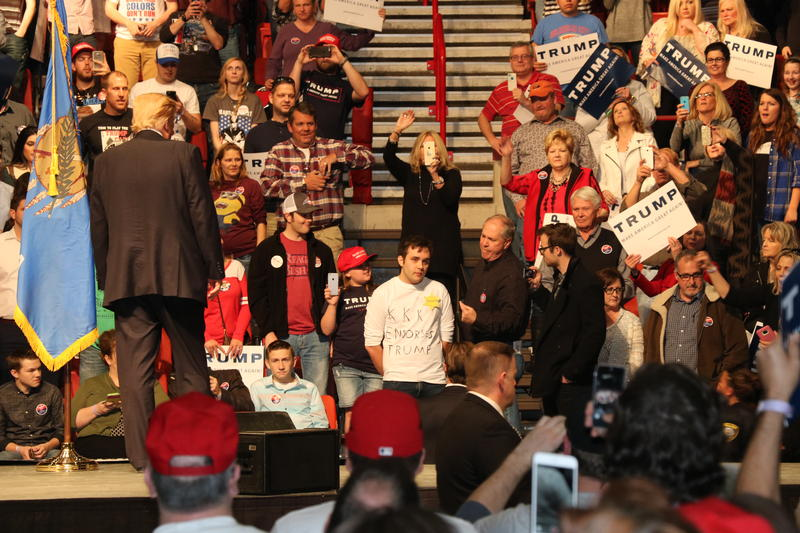 """Donald Trump stares at a protester in a """"KKK Endordes Trump"""" shirt in Oklahoma City on February 26, 2016."""