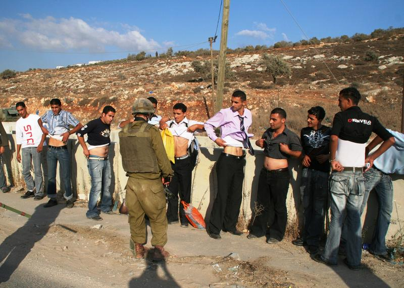 Men at the Awarta checkpoint in the West Bank show their stomachs to prove they're not carrying explosives, October 1, 2006.