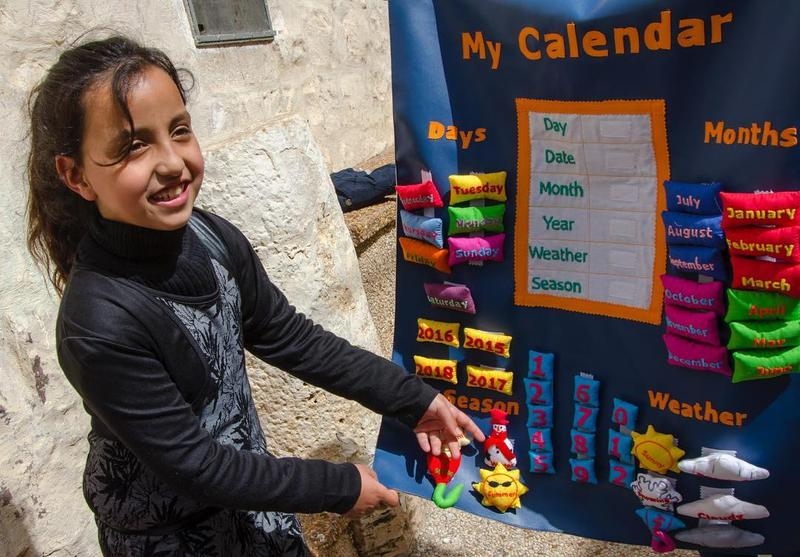 A girl in the West Bank plays with a handmade calendar created by Child's Cup Full