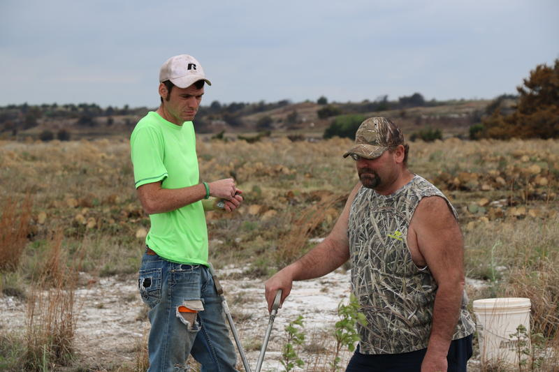Ty Judd and his father, David Wilson, pause during a rattlesnake hunt on April 16, 2016 near Okeene, Oklahoma.
