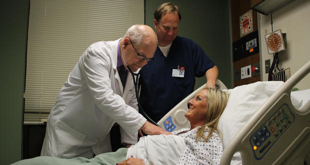 Dr. Billy D. Schumpert, left, checks on Debbie Brewer at Eastern Oklahoma Medical Center in Poteau on Tuesday while Kody Smith, infection preventionist and registered nurse, looks on.