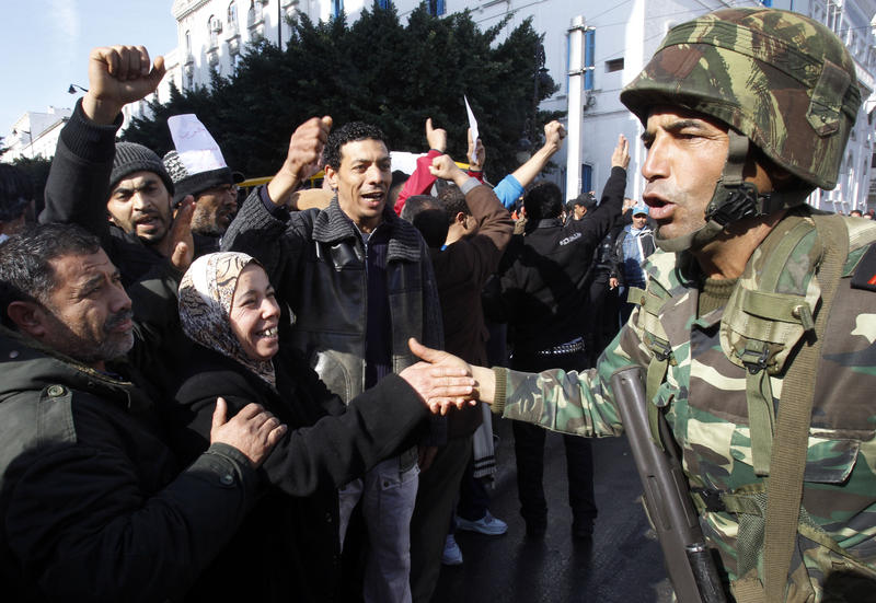 In this Monday, Jan. 17. 2011 file photo protestors greet soldiers during a demonstration against former Tunisian President Zine El Abidine Ben Ali in the center of Tunis.