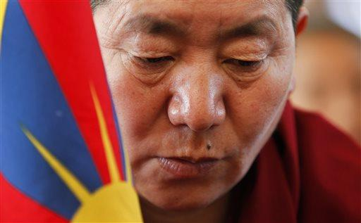 An exile Tibetan prays during an event to mark the 57th anniversary of the March 10, 1959, Tibetan Uprising Day, in Dharmsala, India, Thursday, March 10, 2016.