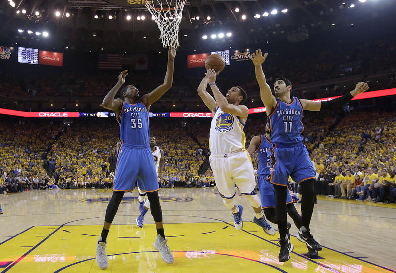 Golden State Warriors guard Stephen Curry (30) shoots between Oklahoma City Thunder forward Kevin Durant (35) and center Enes Kanter (11) during the first half of Game 7 of the NBA's Western Conference finals in Oakland, Calif., Monday, May 30, 2016