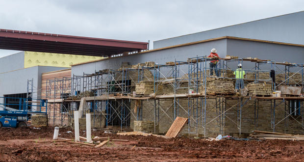 Workers install a stone façade outside one of four Senior Wellness Centers being built as part of Oklahoma City's MAPS 3 program.