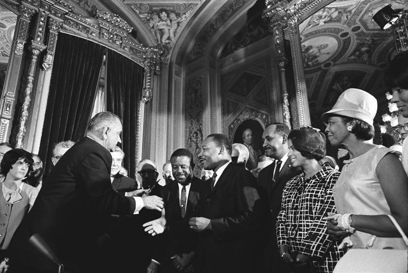 President Lyndon Johnson, left, shakes civil rights leader the Rev. Dr. Martin Luther King, Jr.'s hand immediately after signing the Voting Rights Act, August 6, 1965.
