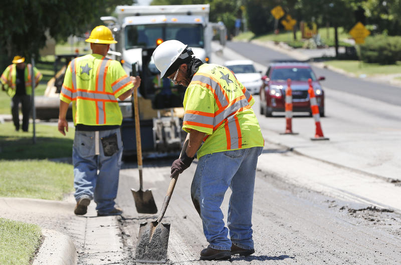Workers repair a road in Oklahoma City, July 9, 2014.