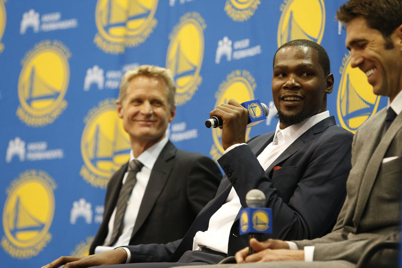 Golden State Warriors' Kevin Durant, center, speaks as coach Steve Kerr, left and general manager Bob Myers listen during a news conference at the NBA basketball team's practice facility, Thursday, July 7, 2016, in Oakland, Calif.