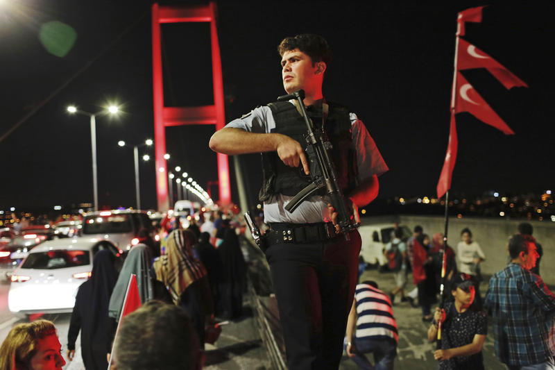 A Turkish police officer patrols as pro-government supporters, gather on Istanbul's iconic Bosporus Bridge, Thursday, July 21, 2016. Turkish lawmakers approved a three-month state of emergency, endorsing new powers for Turkey's President Erdogan.