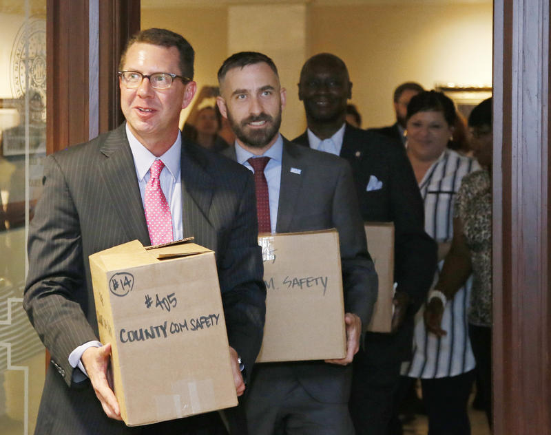 Kris Steele, left, Chair of Oklahomans for Criminal Justice Reform, and Ryan Kiesel, second from left, Executive Director, American Civil Liberties Union of Oklahoma, deliver petitions to the Oklahoma Secretary of State