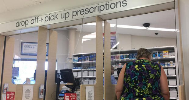 A customer picks up her prescription at the pharmacy counter inside Walgreens at 1400 E. Second St. in Edmond.