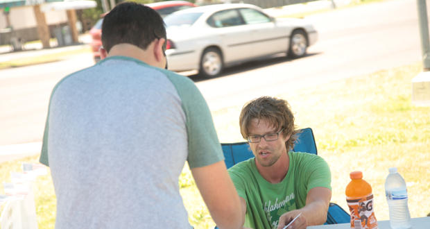 A volunteer with Oklahomans for Health hands a passerby a petition to sign at the group's tent at Northwest Expressway and Meridian Avenue in Oklahoma City. The group is collecting signature for a ballot initiative that would legalize marijuana.