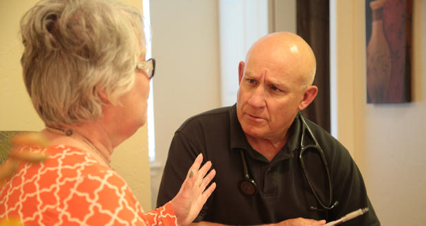 Dr. Scott Dellinger talks with a patient at Willowood at Mustang senior living center in Mustang.