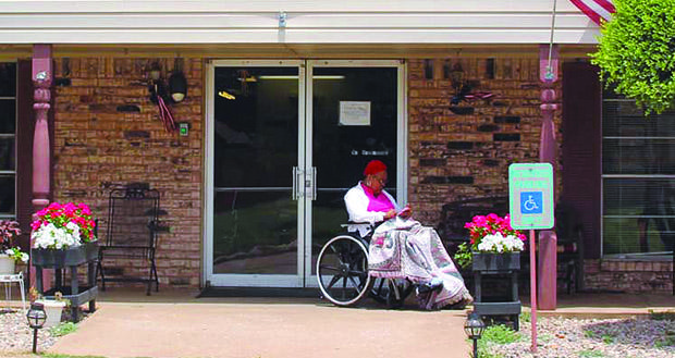 A resident sits outside Hennessey Care Center. The nursing home is one of six in the state that will be transferred into receivership while the landlord finds a new operator.