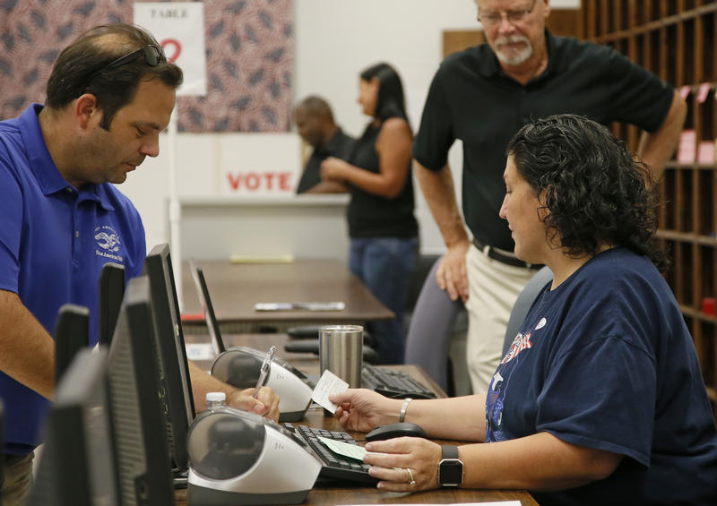 Summerlinn Muhammad, right, elections assistant, checks in Jason Soper, right, for early voting in Oklahoma City, Thursday, Aug. 18, 2016.