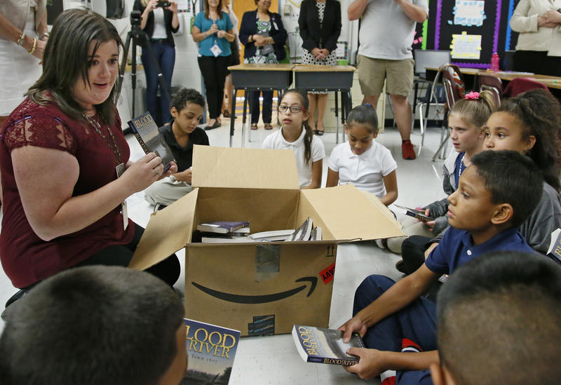 Monta Johnson, a fifth-grade teacher at Adams Elementary School, passes out books to her class in Oklahoma City on August 3, 2016.