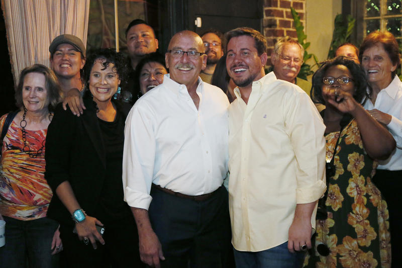 Former state Sen. Al McAffrey (left center) poses with his partner, David Stinson, and other supporters as they take a group photo during his August 23, 2016 night watch party for run-off election in the Democratic race for the 5th Congressional District.