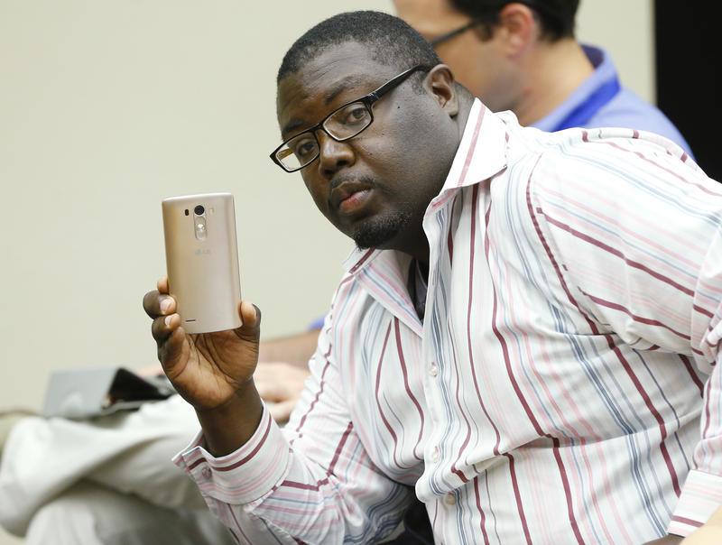 Marq Lewis, of We The People, videos a speaker at a county commissioner's meeting, concerning Sheriff Stanley Glanz, in Tulsa, Okla., Monday, July 13, 2015.